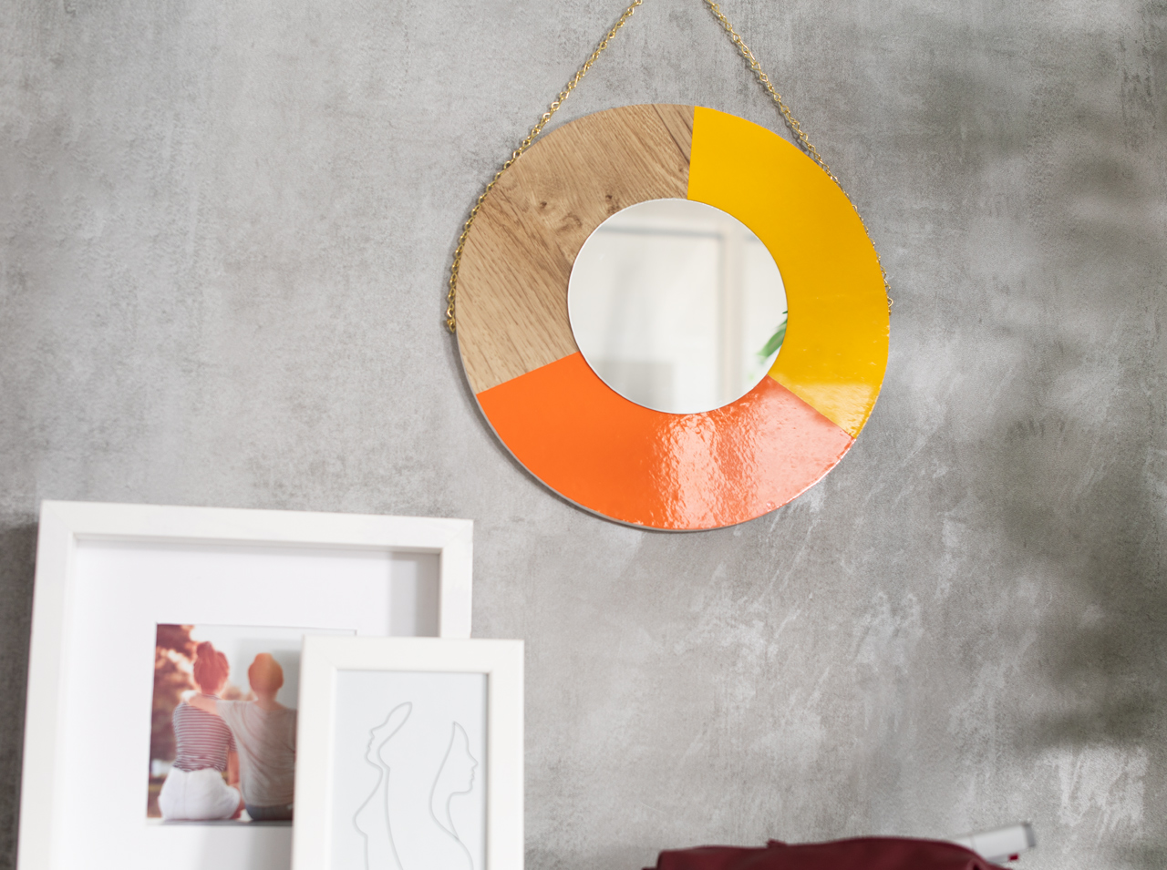 Runder DIY Wandspiegel mit Farbkombination aus Klebefolien an Kette aufgehängt