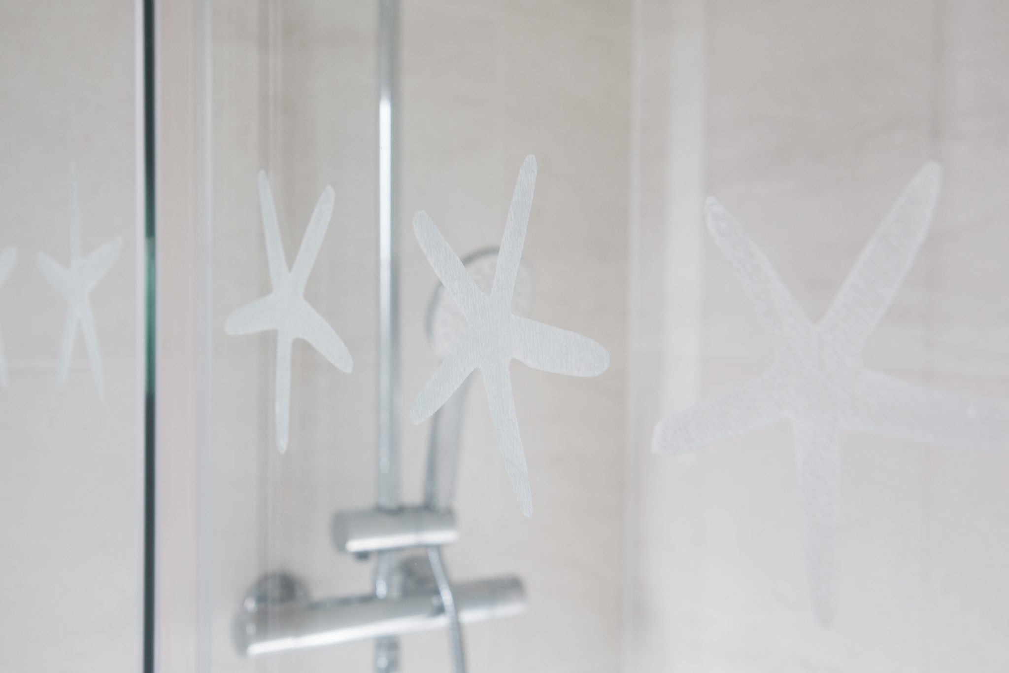 Glass shower enclosure with starfish made from d-c-fix® Opal adhesive film.