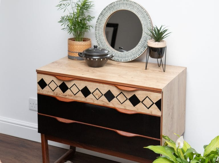 Chest of drawers covered with d-c-fix® adhesive films in a boho look with wood effect and decorative elements in black.
