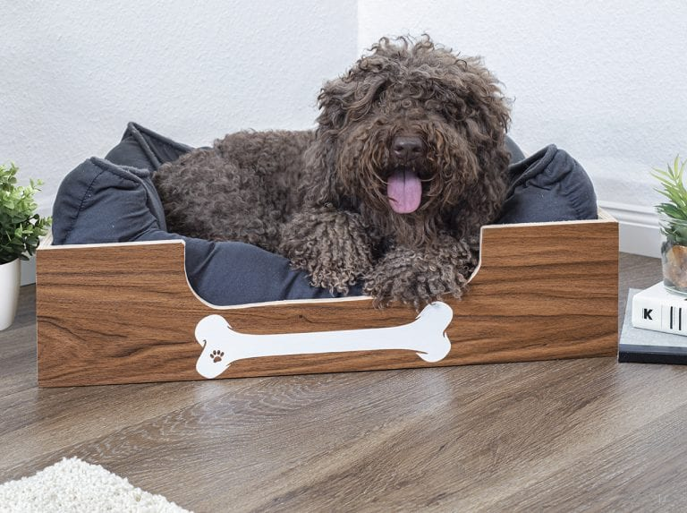 Box with d-c-fix® adhesive foil in wood look and white bone-sticker as an attractive sleeping area for dogs.