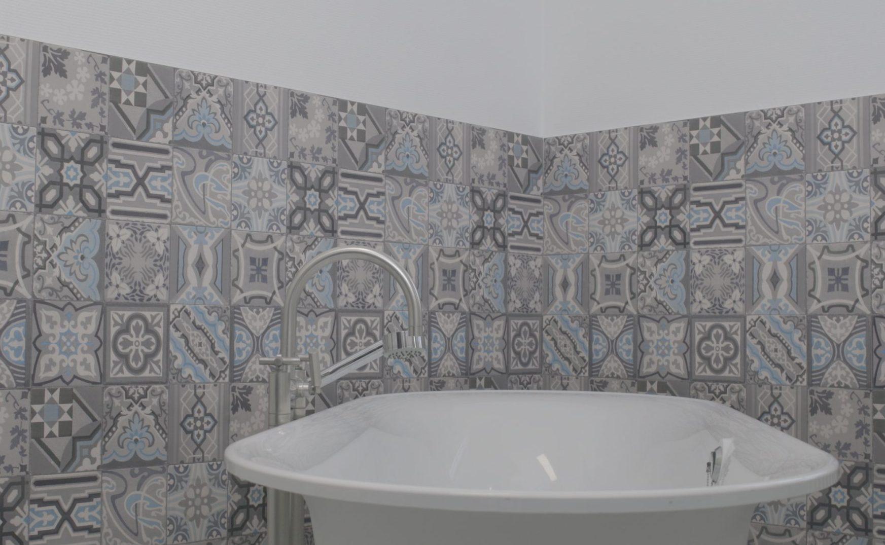 Parete piastrellata del bagno appena rivestita con la carta da parati d-c-wall® ceramics Simenta con l'aspetto di piastrelle decorative.