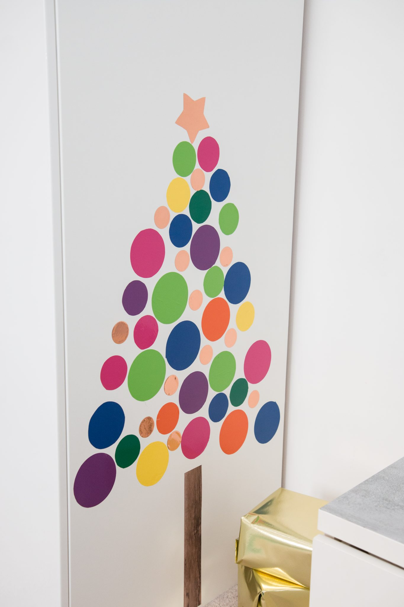 Various colorful circles made from d-c-fix® adhesive foils arranged in the form of a Christmas tree and stuck on.