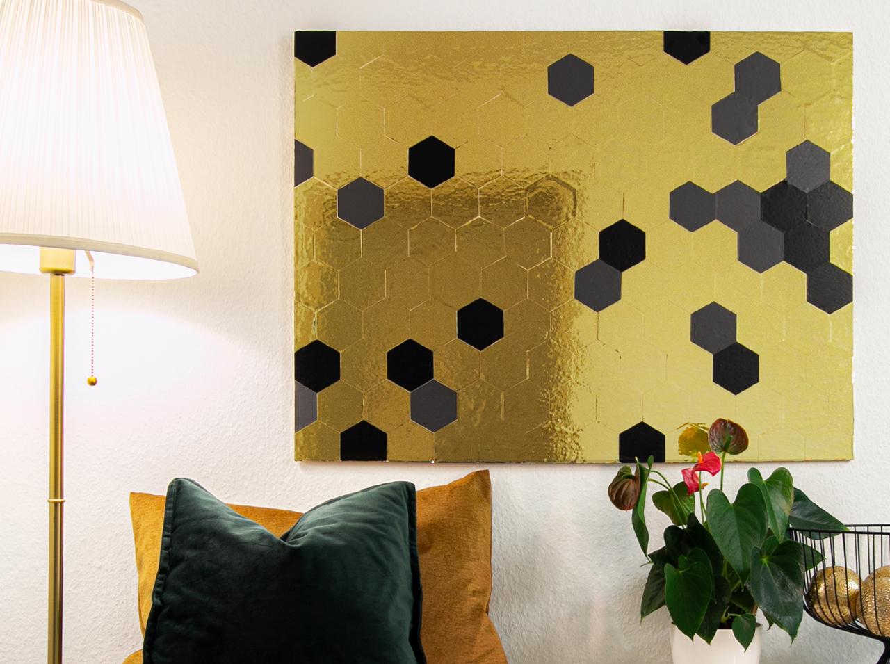 Obraz ścienny DIY na drewnianej płycie z geometrycznym wzorem plastrów miodu wykonanych z folii d-c-fix® w kolorze złotym, antracytowym i czarnym.